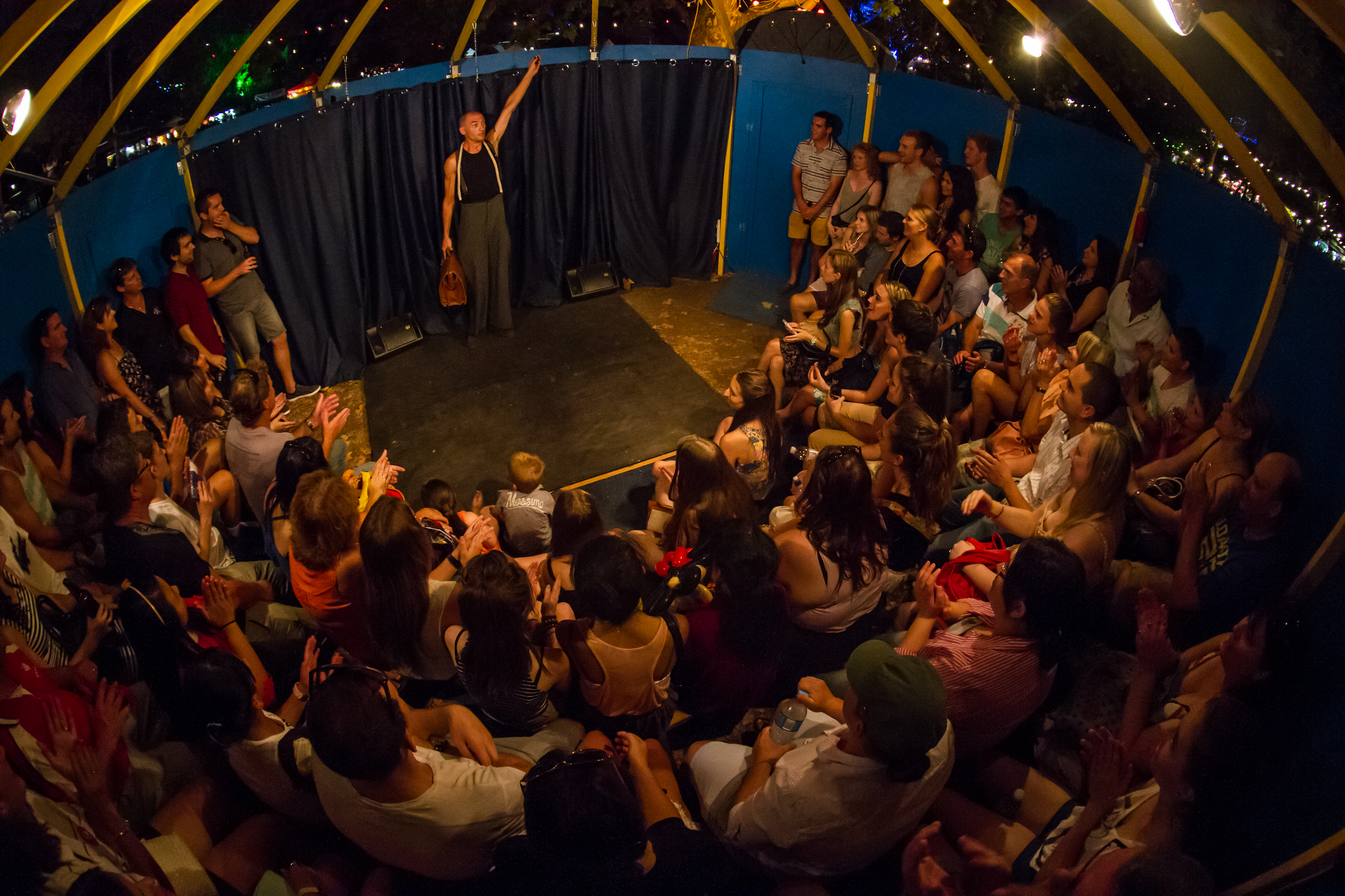 Circus performer on stage, surrounded by the audience, inside a big top tent.